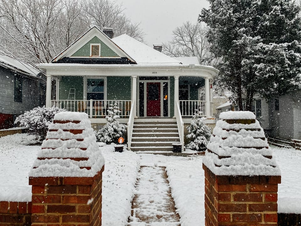 green-and-white-house-in-snow