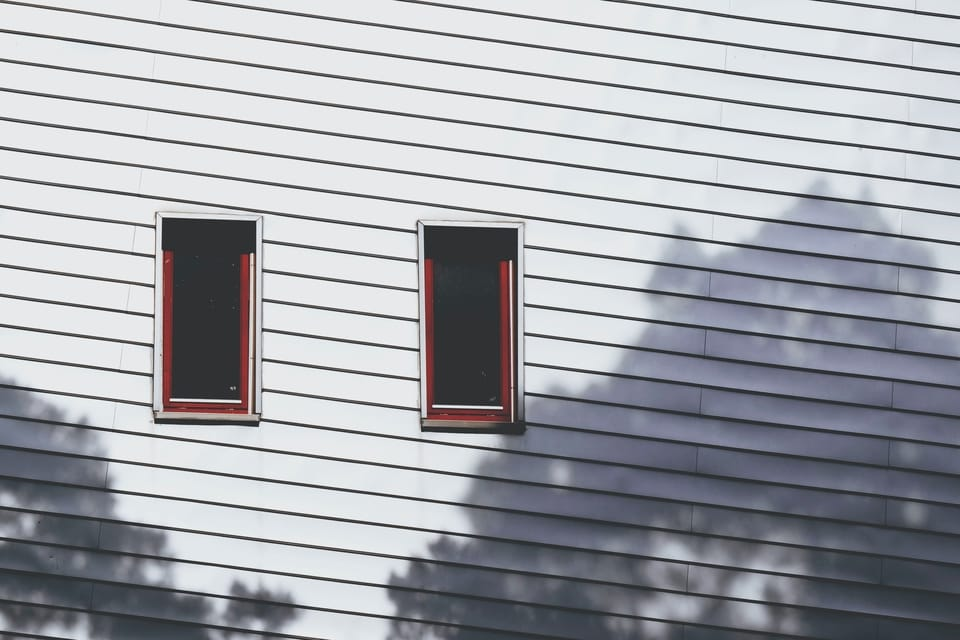 white-siding-and-two-windows-on-house